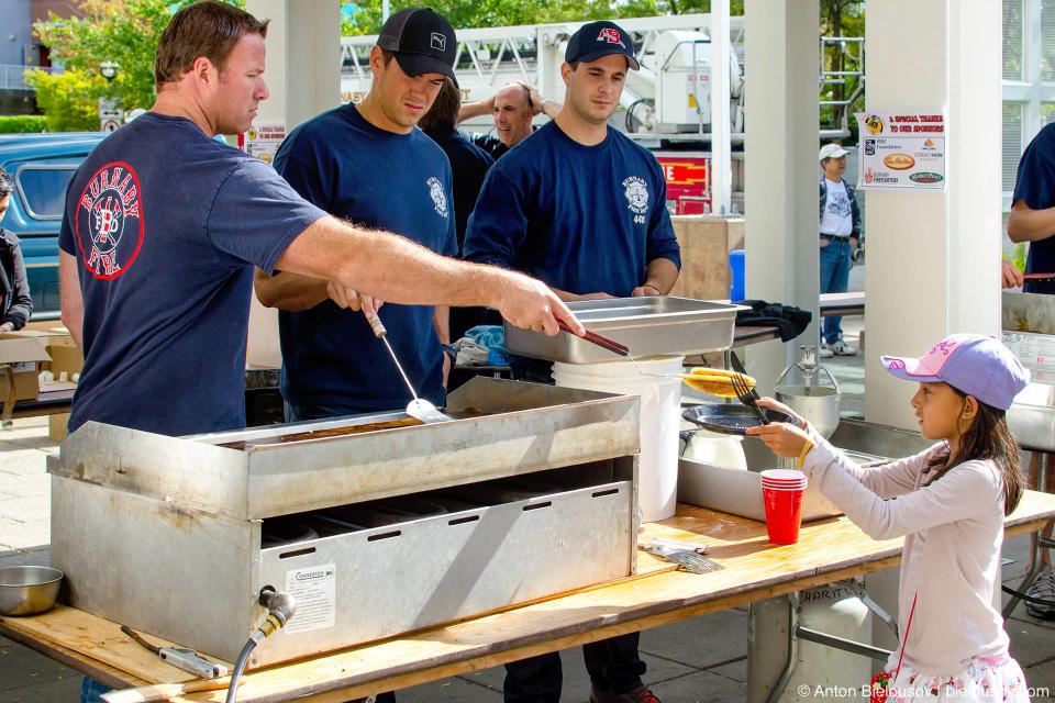 Утром перед зданием библиотеки волонтеры из пожарного депарамента готовят блинчики.