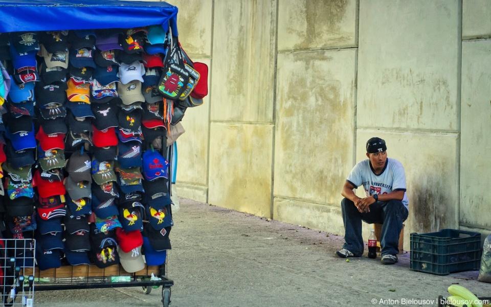 Мексиканский торговец головными уборами под мостом в Канкуне