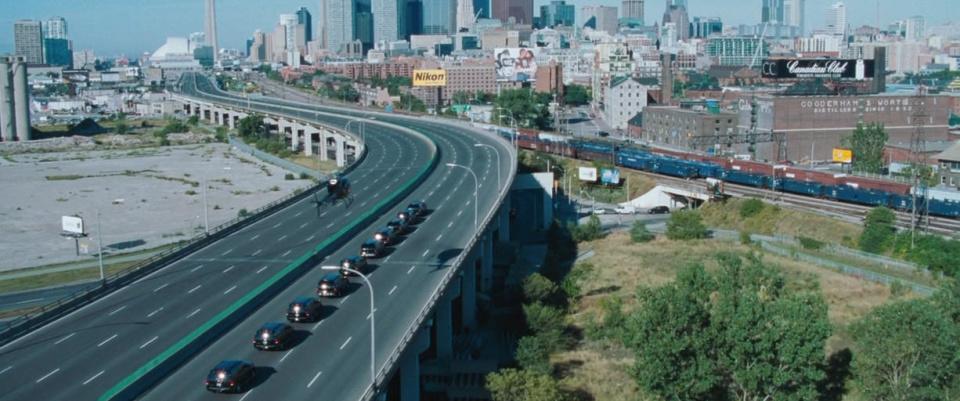 Resident Evil: сцена с автоколонной, движущейс як городу Raccoon City, в которой мелькает основании башни CN Tower