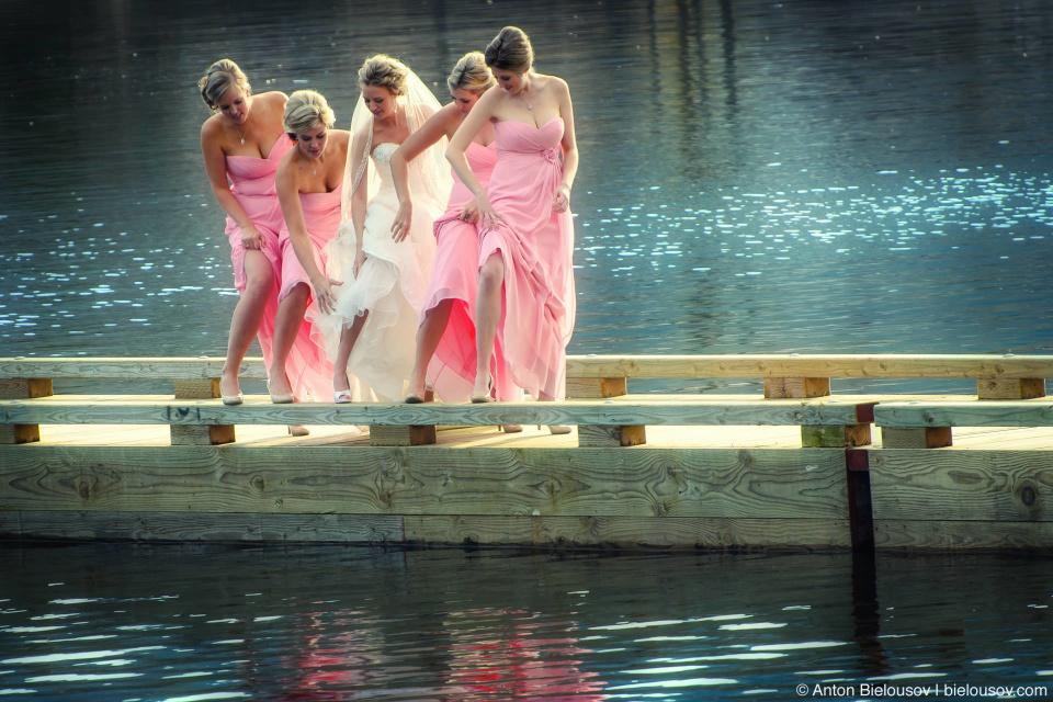 Свадебное фото на причале в Порт Муди: невеста и подружки показывают ножки