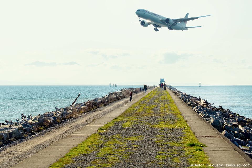 Самолет заходит на посадку в междуародный аэропорт Ванкувера YVR над косой Iona Jetty