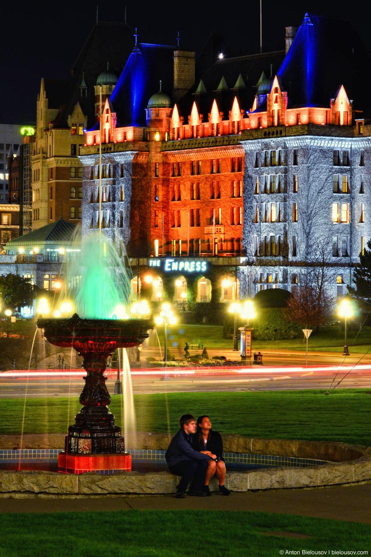Романтичная пара поздно вечером у фонтана перед зданием Пардамента Британской Колумбии в Виктории
