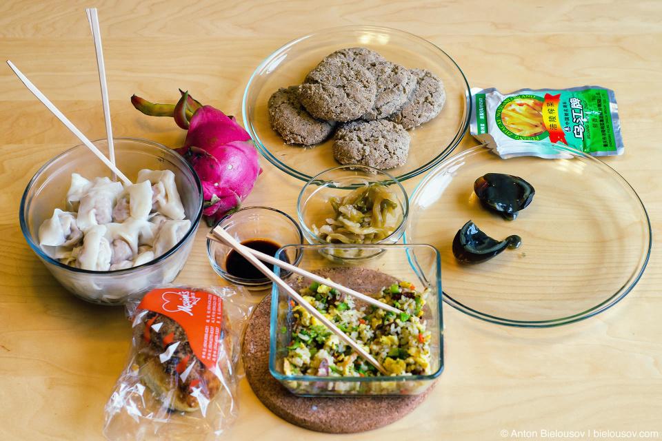 Настоящая традиционная китайская кухня (слева направо, сверху вниз): дамплинги с креветками и свининой, питайя, соевый соус, сладкая булка с присыпкой из волокон вяленой свинины, печеньки с черным сезамом, маринованные побеги горчицы, рис с яйцом и традиционными сосисками, та же горчица в пакетике и столетнее яйцо