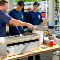Утром перед зданием библиотеки волонтерны из пожарного депарамента готовят блинчики.