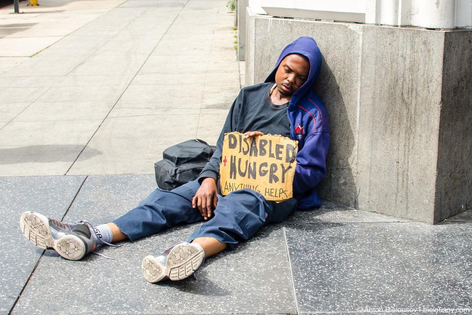Спещий бездомный с кровью на лице на Аллее Славы в Голливуде